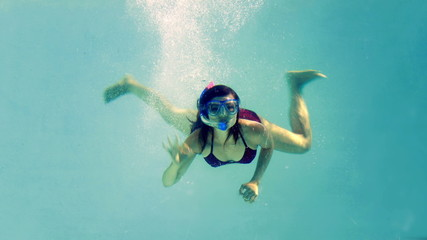 Fit brunette diving into swimming pool wearing snorkel