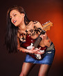 Aggressive girl with tattoo playing guitar.