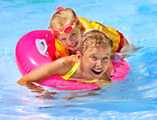 Children in life jacket at swimming pool.