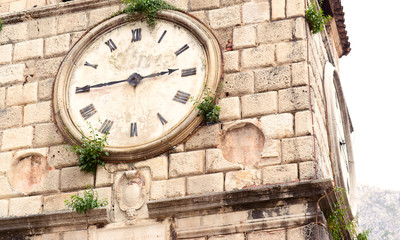 Old clock on a stone wall inside the town of Kotor