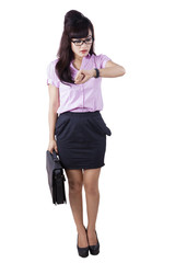 Full length businesswoman looking at wristwatch