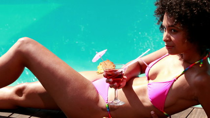 Sexy brunette relaxing poolside with cocktail