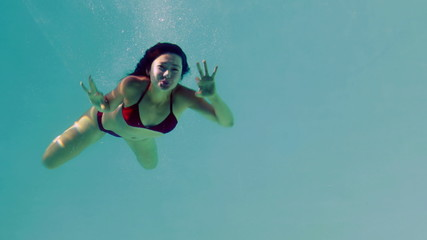 Pretty brunette diving into swimming pool and waving