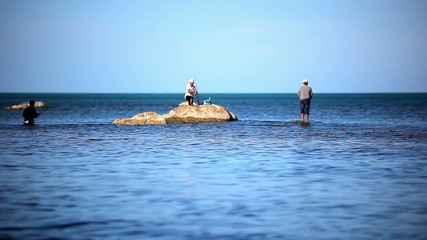 Fishermans at the sea standing on stones go fishing. Video in