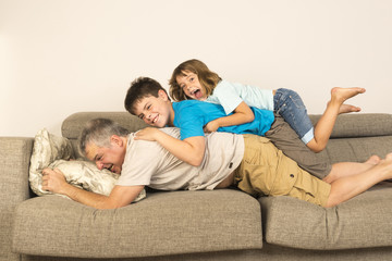 father and kids playing on the sofa
