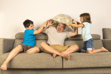 Dad and kids fighting together with pillows