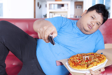 Obese man holds pizza and remote 1