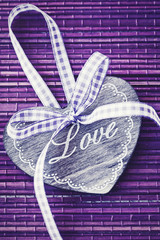 Wooden Heart (with love) on a purple background.Vintage style.