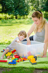 Cute baby boy plays toys with young mother in park