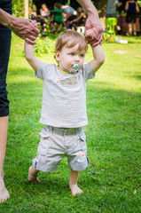 Little cute baby boy  walking with mother in park