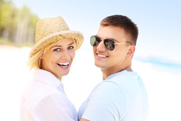 Young couple smiling at the beach