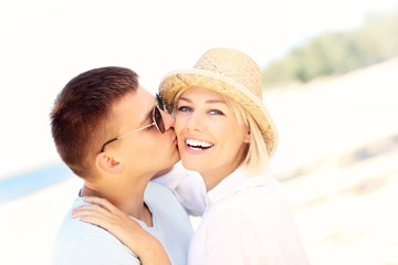 Man kissing a woman at the beach