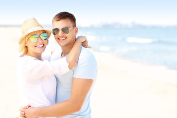 Adult happy couple hugging at the beach