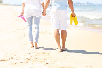 Couple walking at the beach and carrying flip flops