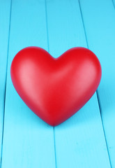 Decorative red heart close-up on blue wooden table