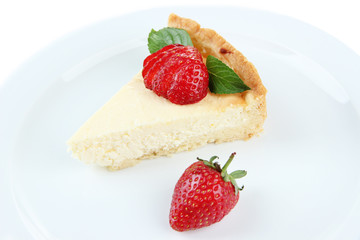 Slice of cheesecake with strawberry on plate, isolated on white
