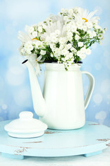 Beautiful chamomiles in teapot on table on bright background
