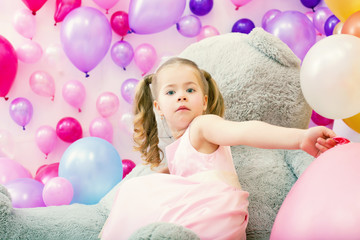 Surprised girl posing at camera with balloons