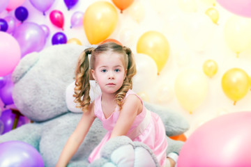 Funny little girl playing in studio with balloons