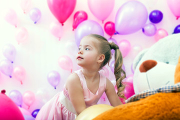 Pretty little lady posing on balloons backdrop