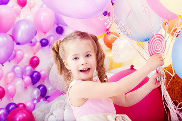 Merry little girl posing with bunch of balloons