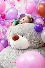 Cute curly girl posing lying on big plush bear