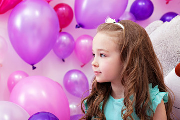 Beautiful little girl on background of balloons