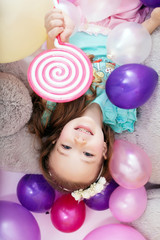 Top view of merry little girl posing with balloons