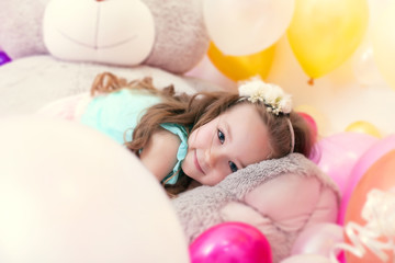 Adorable little girl lying on plush bear