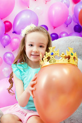 Cheerful girl playfully put crown on balloon