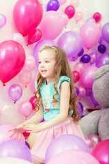 Image of cute little girl playing among balloons