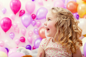 Adorable cheerful girl on balloons background