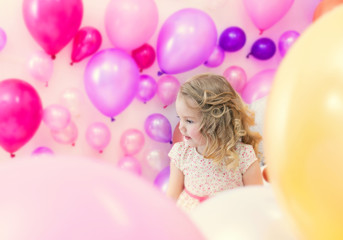 Pretty girl posing in studio where lot of balloons