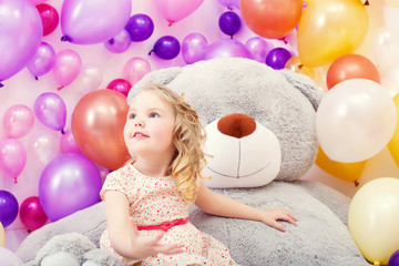 Funny little girl posing with big teddy bear