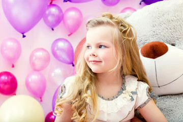 Smiling pretty blonde girl posing in playroom