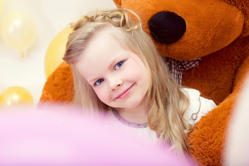 Smiling blue-eyed girl posing with teddy bear