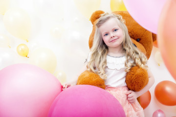 Smiling blonde girl playing with teddy bear