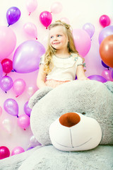 Smiling little girl posing with plush bear