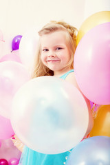 Funny little girl posing with balloons