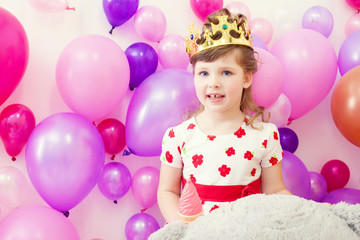 Cute girl posing in crown on balloons background