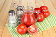 Tomato juice in glass jug, on wooden background