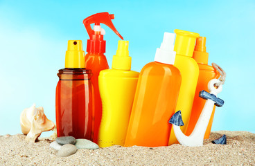 Bottles with suntan cream, on blue background