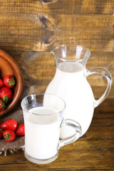 Ripe sweet strawberries in wooden bowl and jug with milk