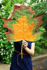 Girl holding decorative maple leaf in park