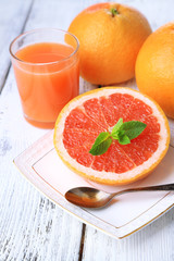 Half of grapefruit, glass of fresh juice and spoon