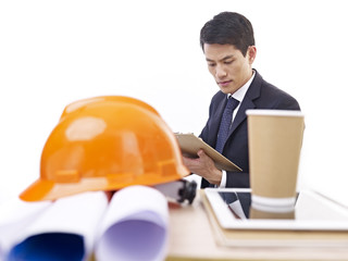 asian construction manager working in office