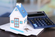 canvas print picture - Toy house and calculator on table close-up