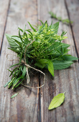 bunch of fresh herbs on wooden rustic planks