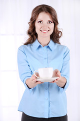 Young business woman with cup in room