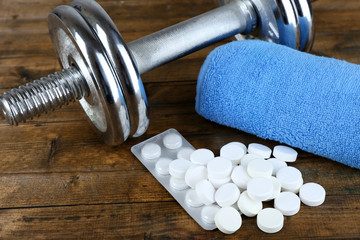 Dumbbell, syringe and tablets on wooden background